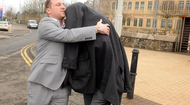 A friend shields Michael Croome from cameras as he leaves Antrim Courthouse - Michael Croome, 28, was sentenced in Antrim Court today. He had been charged with causing death by dangerous driving.