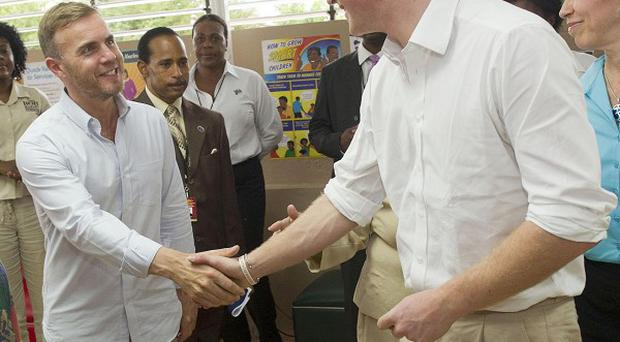 Prince Harry meets Gary Barlow during his visit to a youth community centre in Kingston, Jamaica