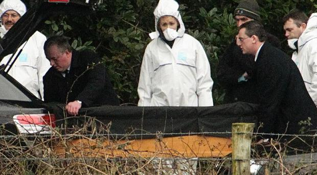 Gardai remove one of the bodies at Ravensdale Park near Dundalk