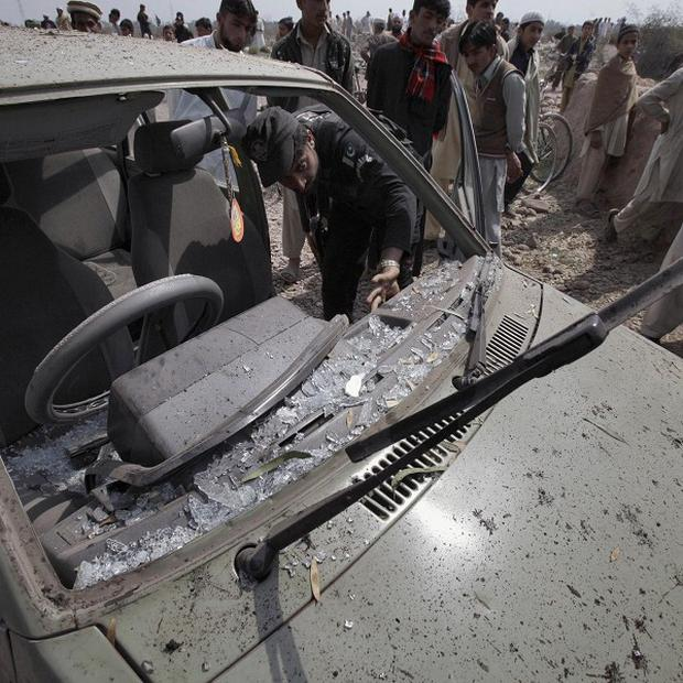 A Pakistani police officer and local residents examine a parked car damaged in suicide bombing in on the outskirts of Peshawar, Pakistan (AP)
