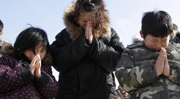 A family observes a moment of silence in front of what is left of a disaster control center in an area devastated by the 2011 earthquake (AP)