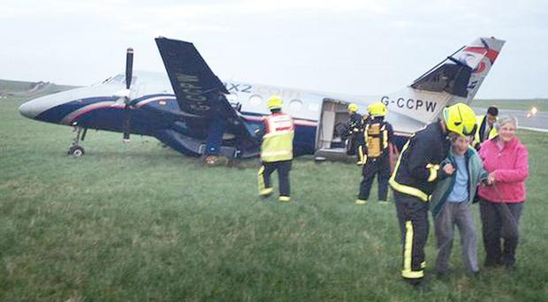 Taken to safety: Rescue workers lead dazed passengers from the Manx2 plane that crashed on the Isle of Man