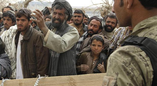 An Afghan soldier speaks to civilians outside a military base after a US soldier killed more than a dozen people (AP)