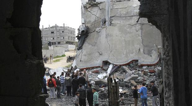 Palestinians inspect the rubble of a destroyed building following an Israeli airstrike (AP)