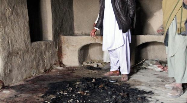 Men stand next to blood stains inside a home where witnesses say Afghans were killed by a US soldier in Panjwai, Kandahar province (AP)
