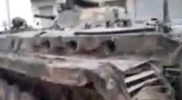 An image made from amateur video purporting to show a Syrian rebel on top of a military tank in Khan Sheikhoun (AP)