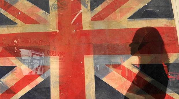 A member of the public casts a shadow on a Union flag recovered from Ground Zero amongst the wreckage of the 9/11 attack