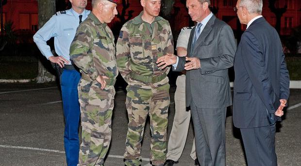 French defence minister Gerard Longuet, centre, speaks with soldiers at the site of the shooting(AP)