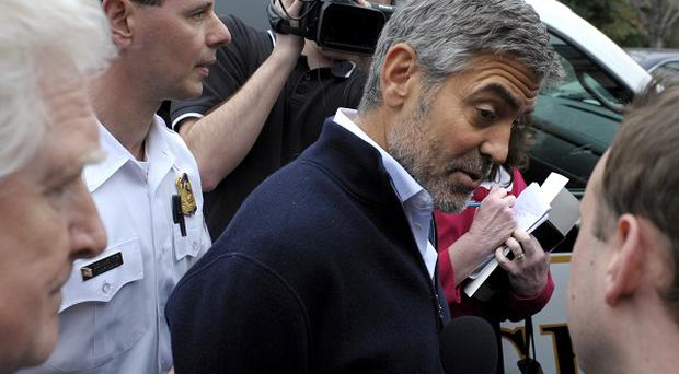 George Clooney is arrested during a protest at the Sudan Embassy in Washington (AP)