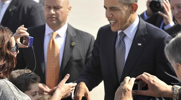 US president Barack Obama greets supporters after arriving at O'Hare International Airport in Chicago (AP)