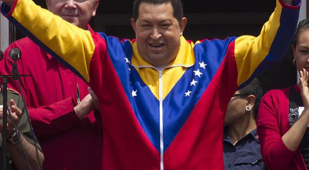 Venezuela's President Hugo Chavez gestures to supporters from a balcony at Miraflores presidential palace in Caracas (AP)