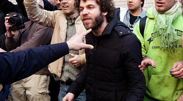 An Occupy Wall Street demonstrator is pushed back from the scene of an arrest by a police officer (AP)