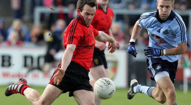 Pressing on: Down's Mark Poland takes on Dubln's Jonny Cooper Sunday's NFL clash in Newry