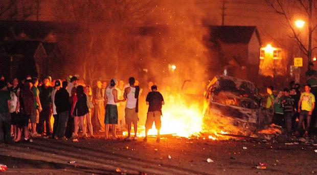 St Patrick's Day revellers stoke a fire with trees and sections of fencing in London, Canada (Canadian Press, Mike Maloney)