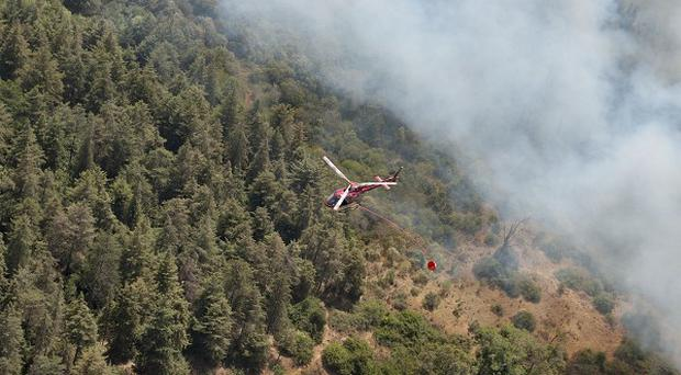 A helicopter drops water in an attempt to put out a fire on the slopes of Mount Kenya (AP)