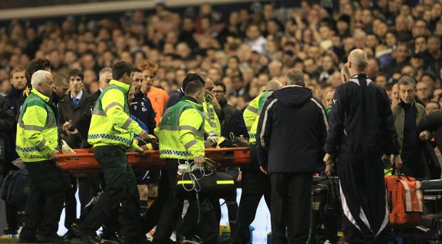 LONDON, ENGLAND - MARCH 17: Dr Andrew Deaner (far right) walks off the pitch as Fabrice Muamba of Bolton Wanderers is taken off on a stretcher, still unconscious after receiving CPR treatment on the pitch after suddenly collapsing during the FA Cup Sixth Round match between Tottenham Hotspur and Bolton Wanderers at White Hart Lane on March 17, 2012 in London, England. The game was abandoned. (Photo by Richard Heathcote/Getty Images)