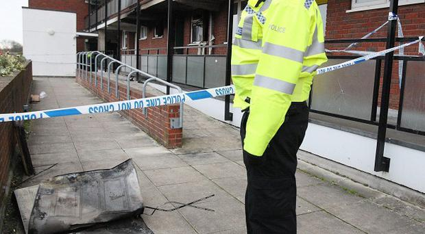 A woman has died after an explosion at a flat in Guildford, Surrey and a man suffered life threatening injuries