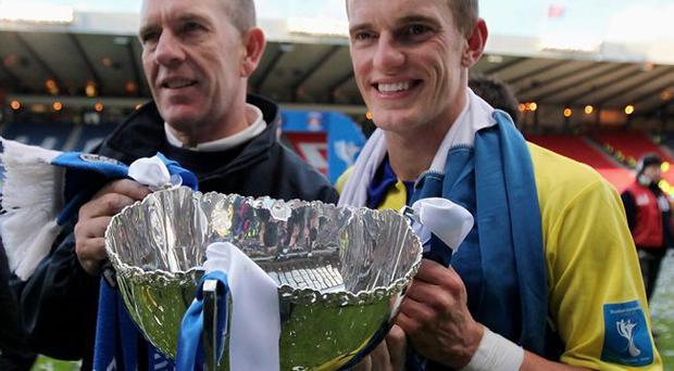 Father figure: Kenny Shiels shows off the Scottish League Cup trophy with son Dean