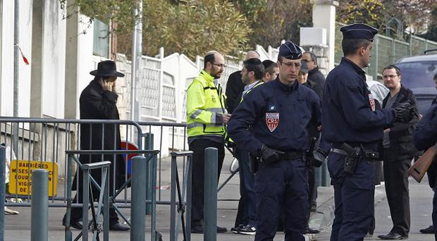 Police officers stand guard at the entrance of the Ozar Hatorah Jewish school in Toulouse where a gunman killed four people (AP)
