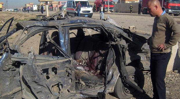 A man stands next to a destroyed vehicle at the scene of a car bomb attack in Kirkuk (AP)