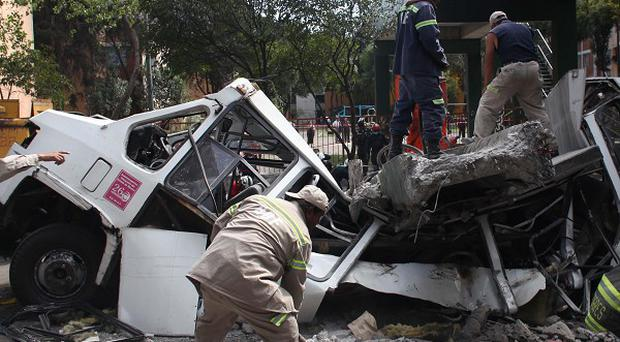 Firefighters work to remove a cement beam that fell from a bridge onto a public bus after an earthquake in Mexico City (AP)