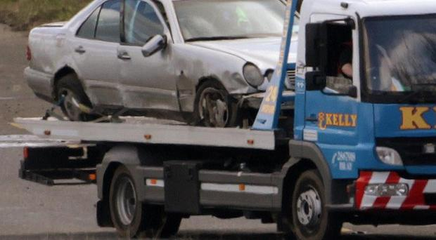 A car is removed from the scene after an off duty Garda officer was killed in a road accident