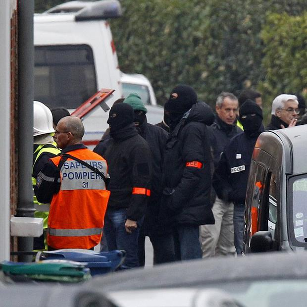 Police officers surround the building in Toulouse, where the shooting suspect is holed up (AP)