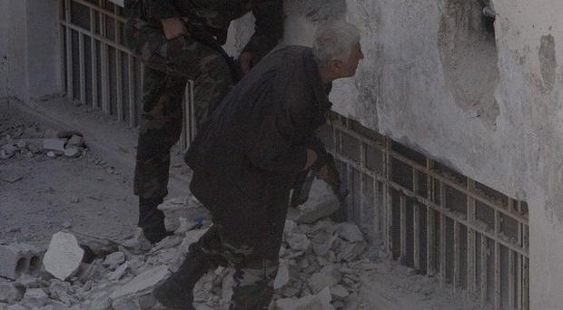 Syrian army soldiers search a building for rebels in a suburb of Damascus (AP)