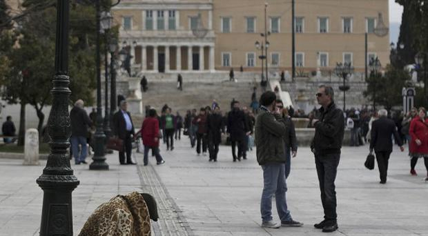 A homeless person begs in Syntagma square, backdropped by the Greek Parliament in Athens (AP)