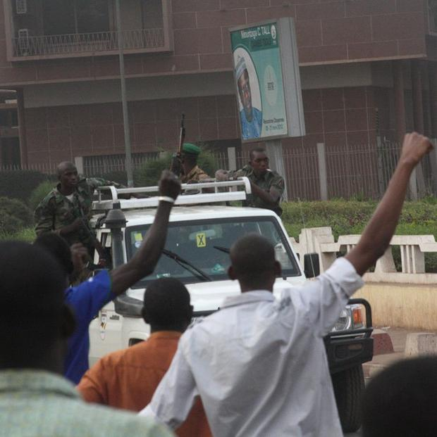 Civilians cheer as soldiers drive past in Bamako, Mali ahead of the storming of the state TV and radio station (AP)