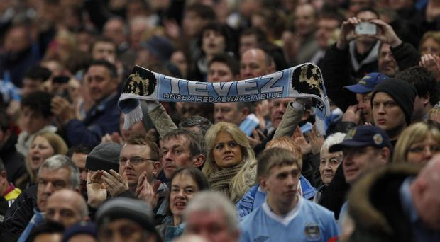 A fan in the stands holds a 'Tevez' scarf during the Barclays Premier League match at the Etihad Stadium, Manchester