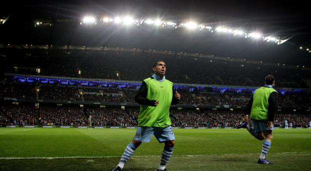 Manchester City's Carlos Tevez warms up during the Barclays Premier League match at the Etihad Stadium, Manchester