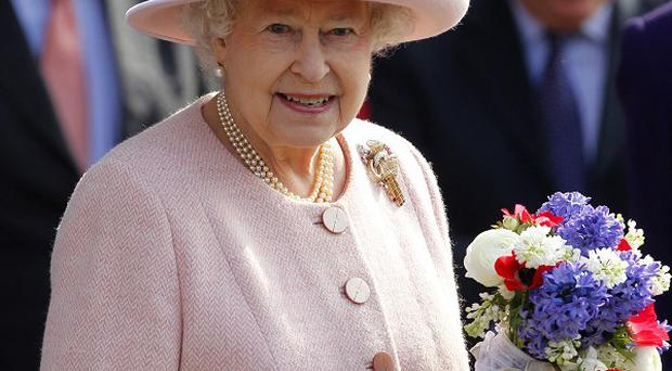 The Queen was wearing a strawberry pink linen dress by Angela Kelly as she greeted the public in Manchester