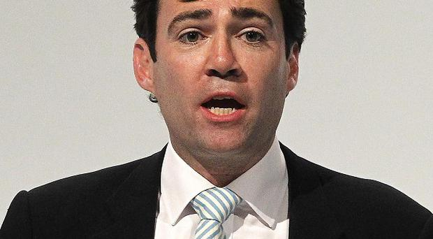 Andy Burnham claimed the NHS is 'taking a hit' to help fund the cut in the top rate of income tax