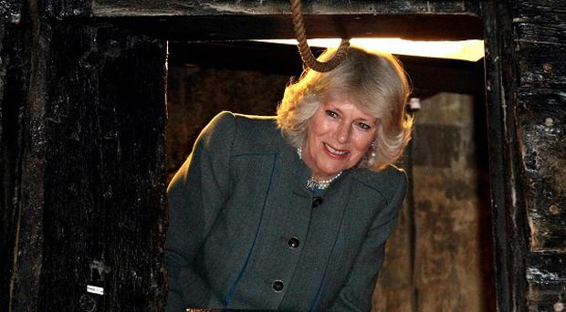 The Duchess of Cornwall peers through a gun turret, during a visit to the warrior ship Vasa