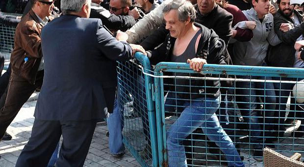 Protesters try to remove barricades as plain clothes police try to stop them in Patras (AP)
