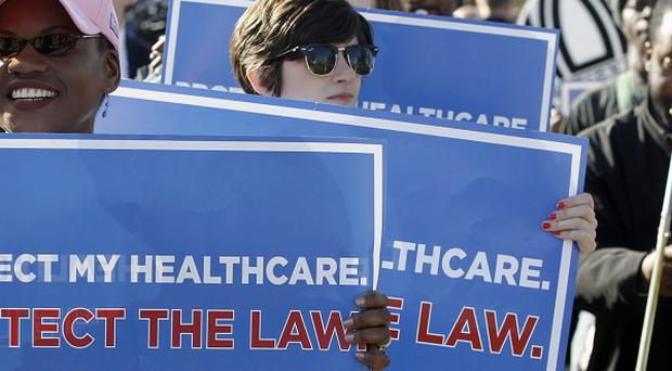 Supporters for Barack Obama's health care reforms gather outside the country's Supreme Court for a vital hearing (AP)