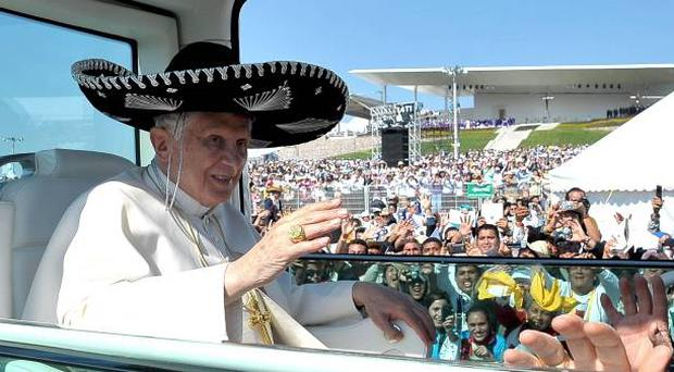 Pope Benedict XVI waves from the popemobile wearing a Mexican sombrero as he arrives to give a Mass in Bicentennial Park near Silao, Mexico