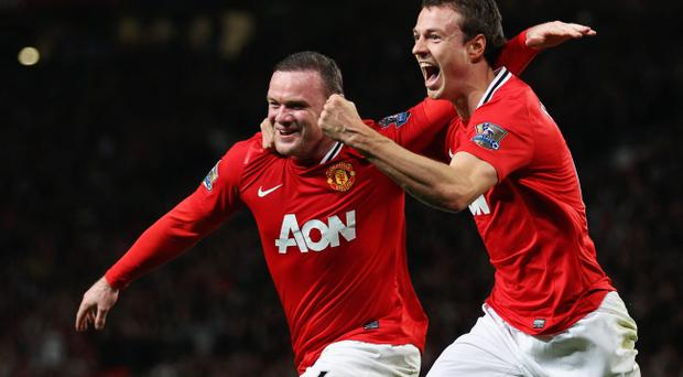 MANCHESTER, ENGLAND - MARCH 26: Wayne Rooney of Manchester United (L) celebrates with Jonny Evans as he scores their first goal during the Barclays Premier League match between Manchester United and Fulham at Old Trafford on March 26, 2012 in Manchester, England. (Photo by Alex Livesey/Getty Images)