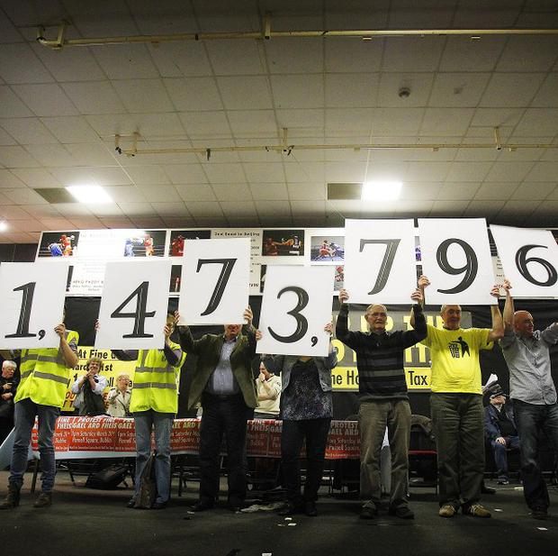 Protesters hold up placards with the estimated number of households which are not registered to pay the household tax
