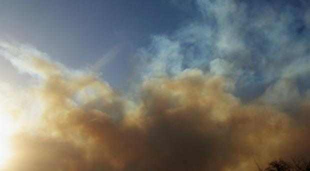A plume of smoke rises from a wildfire burning out of control near Conifer, Colorado (AP/Kris Garrett)
