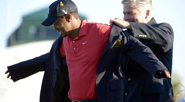 Tiger Woods, left, is presented the jacket for winning the Arnold Palmer Invitational golf tournament at Bay Hill by tournament chairman Don Oehlrich in Orlando, Fla., Sunday, March 25, 2012