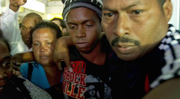 Adrian Vasquez, second from right, is surrounded by family members at Tocumen international airport in Panama City (AP/Arnulfo Franco)