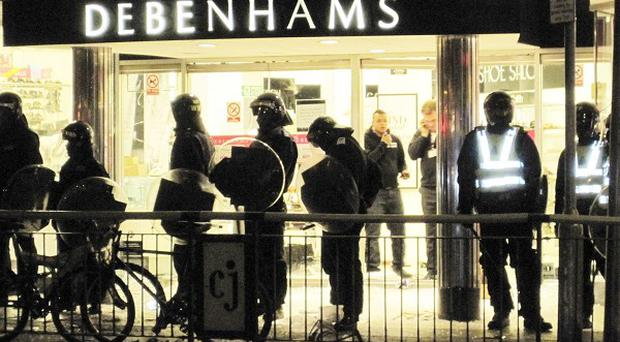 Police stand guard outside Debenhams in Clapham Junction, south London, which was attacked by looters during last summer's riots