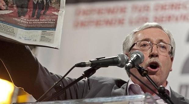 Trade union leader Fernandez Toxo holds up a newspaper with the headline 'The Labor reforms are vital for the recuperation' (AP/Pedro Acosta)
