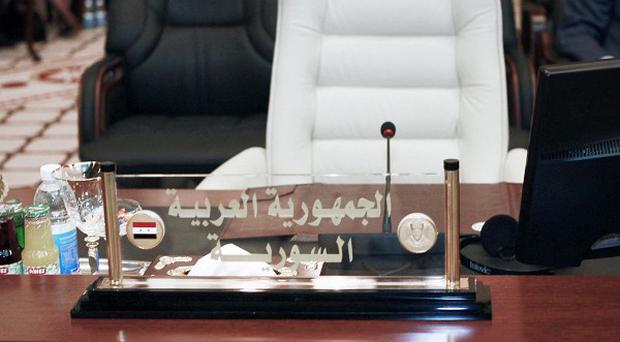 The empty seat of Syria's foreign minister at a meeting of Arab League nations in Baghdad, Iraq (AP)