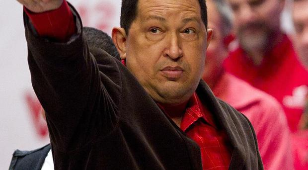 Hugo Chavez gestures during an event at Teresa Carreno theatre in Caracas, Venezuela (AP Photo/Ariana Cubillos)