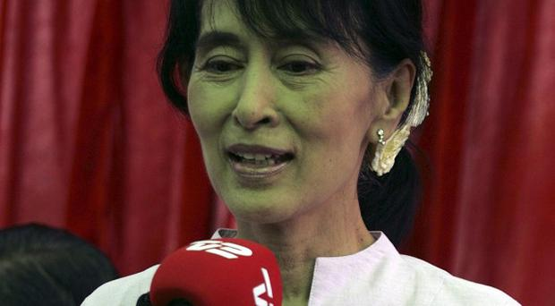 Opposition leader Aung San Suu Kyi talks to reporters during a press conference at her lakeside residence (AP)