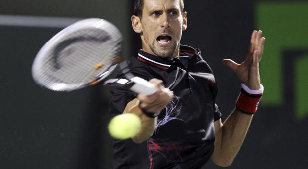 Novak Djokovic, of Serbia, returns the ball to Juan Monaco, of Argentina, during the men's semi-finals at the Sony Ericsson Open tennis tournament in Key Biscayne, Fla., Friday, March 30, 2012. Djokovic won 6-0, 7-6. (AP Photo/J Pat Carter)