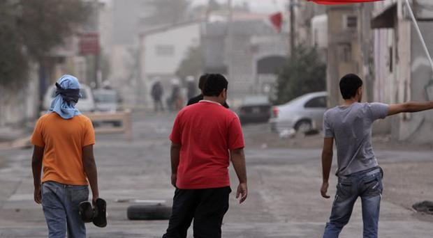 Bahrain anti-government protesters wave a national flag and gesture towards riot police in Sitra (AP)